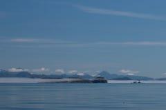 Άποψη των χιονοσκεπών βουνών και των χαμηλών άσπρων σύννεφων πριν από το μπλε ουρανό και απεικόνιση της ήρεμης θάλασσας του Καναδ Στοκ Φωτογραφία