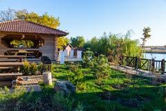 Άποψη φθινοπώρου του πάρκου όχθεων ποταμού με τα ξύλινους σπίτια και τους πάγκους στοκ εικόνες με δικαίωμα ελεύθερης χρήσης