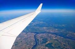 Άποψη φτερών αεροπλάνων του πόλεων γήινου ταξιδιού σύννεφων ουρανού μπλε Στοκ Φωτογραφία