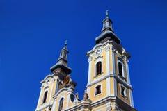 Άποψη χαμηλός-γωνίας των πύργων της ηλιοφώτιστης μπαρόκ εκκλησίας στην Ουγγαρία στοκ φωτογραφία