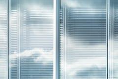 Άποψη louvers του παραθύρου του σύγχρονου κτιρίου γραφείων με την αντανάκλαση του ουρανού με τα σύννεφα, θολωμένη επίδραση στοκ εικόνες