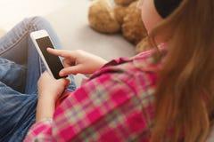Άποψη Overshoulder σχετικά με το μικρό κορίτσι με το smartphone Στοκ εικόνα με δικαίωμα ελεύθερης χρήσης