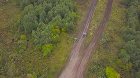 Άποψη SUVs που οδηγά στη λακκούβα συνδετήρας Τοπ άποψη του ξεπεράσματος των λακκουβών SUVs στις φυλές λάσπης Αγώνας τζιπ φιλμ μικρού μήκους