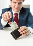 Άπληστος επιχειρηματίας που τραβά το πορτοφόλι χρημάτων έξω με τη χρήση του μαγνήτη Στοκ Εικόνα