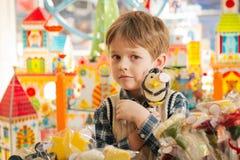Άπληστο αγόρι που κρατά έντονα lollipop στα χέρια Στοκ Φωτογραφίες