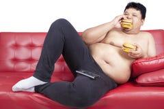 Άπληστο παχύ άτομο που τρώει το χάμπουργκερ 1 στοκ εικόνες