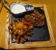Άρθρωση βόειου κρέατος που μαγειρεύεται στη σχάρα Παρουσιασμένος σε μια καυτή πέτρα, με τα ψημένες κρεμμύδια και τη σάλτσα στοκ εικόνες με δικαίωμα ελεύθερης χρήσης