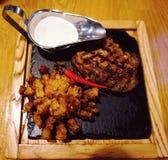 Άρθρωση βόειου κρέατος που μαγειρεύεται στη σχάρα Παρουσιασμένος σε μια καυτή πέτρα, με τα ψημένες κρεμμύδια και τη σάλτσα στοκ εικόνα