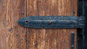 Άρθρωση επεξεργασμένου σιδήρου σε μια παλαιά ξύλινη πόρτα Στοκ φωτογραφία με δικαίωμα ελεύθερης χρήσης
