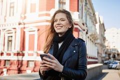Άριστη ημέρα για τις περιπέτειες Πορτρέτο πόλεων του ελκυστικού ευρωπαϊκού περπατήματος κοριτσιών στην οδό, που κρατά το smartpho στοκ εικόνα με δικαίωμα ελεύθερης χρήσης