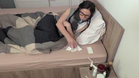Άρρωστη γυναίκα με τη runny μύτη που κρατά το θερμόμετρο στο στόμα φιλμ μικρού μήκους