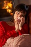 Άρρωστη γυναίκα με το κρύο που στηρίζεται από την άνετη πυρκαγιά κούτσουρων Στοκ Εικόνα