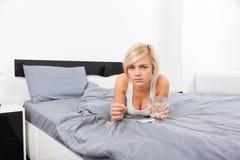 Άρρωστη γυναίκα με το πακέτο των χαπιών που βρίσκονται στο κρεβάτι Στοκ εικόνα με δικαίωμα ελεύθερης χρήσης