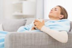 Άρρωστη γυναίκα με το φλυτζάνι της καυτής συνεδρίασης ποτών στον καναπέ Στοκ Εικόνες