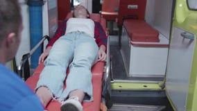 Άρρωστη γυναίκα ξαπλώνει στο φορείο με το ασθενοφόρο απόθεμα βίντεο