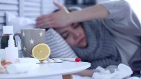 Άρρωστη γυναίκα που βρίσκεται στο κρεβάτι με τη γρίπη στην γκρίζα κρεβατοκάμαρα φιλμ μικρού μήκους