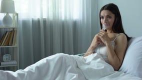 Άρρωστη γυναίκα που εισπνέει τα φάρμακα μέσω nebulizer στο κρεβάτι, αναπνευστική ασθένεια απόθεμα βίντεο