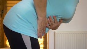 Άρρωστη γυναίκα που κάθεται επάνω από το κρεβάτι που πάσχει από τους επίπονους αρμοσφίκτες στομαχιών λόγω της δυσπεψίας απόθεμα βίντεο
