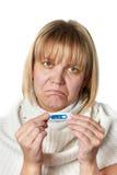 Άρρωστη γυναίκα που κρατά το ψηφιακό θερμόμετρο απομονωμένο Στοκ Εικόνες