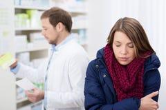 Άρρωστη γυναίκα που περιμένει σε ένα φαρμακείο Στοκ Φωτογραφίες