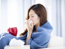 Άρρωστη γυναίκα που φυσά τη μύτη της καθμένος στον καναπέ στοκ εικόνα με δικαίωμα ελεύθερης χρήσης