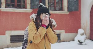 Άρρωστη γυναίκα που φυσά τη μύτη της στον ιστό υπαίθρια Χειμερινός κρύος καιρός απόθεμα βίντεο