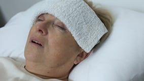 Άρρωστη ηλικιωμένη γυναίκα με την πετσέτα στο μέτωπο που βρίσκεται στο κρεβάτι, που πάσχει από το κρύο ή τη γρίπη απόθεμα βίντεο