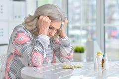 Άρρωστη ηλικιωμένη γυναίκα με τα φάρμακα στοκ εικόνα