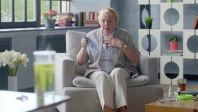 Άρρωστη ηλικιωμένη γυναίκα που βήχει και που κρατά το κεφάλι στο υπόβαθρο του φαρμάκου ιατρικής στο φλυτζάνι του νερού απόθεμα βίντεο