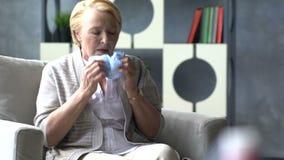 Άρρωστη ηλικιωμένη γυναίκα που βήχει και που κρατά το κεφάλι στο υπόβαθρο του φαρμάκου ιατρικής στο φλυτζάνι του νερού φιλμ μικρού μήκους