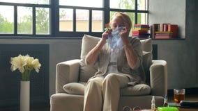Άρρωστη ηλικιωμένη γυναίκα που βήχει και που φυσά πολύ τη μύτη στο χαρτομάνδηλο απόθεμα βίντεο