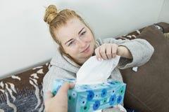 Άρρωστη και κουρασμένη γυναίκα με μια συνεδρίαση πονοκέφαλου σε έναν καναπέ που ρωτά τα FO στοκ εικόνες