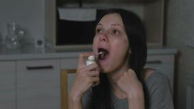 Άρρωστη νέα γυναίκα που χρησιμοποιεί το αερόλυμα ψεκασμού λαιμού στην κουζίνα τη νύχτα Επεξεργασία των κρύων στο σπίτι απόθεμα βίντεο