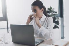 Άρρωστη συνεδρίαση γυναικών στον εργασιακό χώρο της στο γραφείο Μια γυναίκα φυσά τη μύτη της στον εργασιακό χώρο Στοκ εικόνα με δικαίωμα ελεύθερης χρήσης