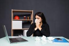 Άρρωστη συνεδρίαση γυναικών στον εργασιακό χώρο της στο γραφείο Μια γυναίκα φυσά τη μύτη της στον εργασιακό χώρο Στοκ Φωτογραφίες