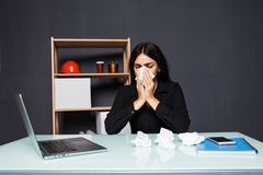 Άρρωστη συνεδρίαση γυναικών στον εργασιακό χώρο της στο γραφείο Μια γυναίκα φυσά τη μύτη της στον εργασιακό χώρο Στοκ φωτογραφία με δικαίωμα ελεύθερης χρήσης