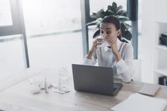 Άρρωστη συνεδρίαση γυναικών στον εργασιακό χώρο της στο γραφείο Φυσά τη μύτη της στον εργασιακό χώρο Στοκ φωτογραφία με δικαίωμα ελεύθερης χρήσης