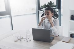 Άρρωστη συνεδρίαση γυναικών στον εργασιακό χώρο της στο γραφείο Φυσά τη μύτη της στον εργασιακό χώρο Στοκ Εικόνα