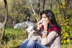 Άρρωστη χαλάρωση γυναικών στο πάρκο φθινοπώρου με το σκυλί της στοκ εικόνα με δικαίωμα ελεύθερης χρήσης
