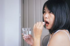 Άρρωστοι γυναικών με το χάπι που υποβάλλουν το στόμα της, θηλυκό που παίρνει τα φάρμακα και ένα ποτήρι του νερού στοκ εικόνες