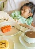 Άρρωστος ασιατικός ασθενής νοσοκομείου παιδιών στο κρεβάτι με τις επιλογές γεύματος προγευμάτων Στοκ Φωτογραφία