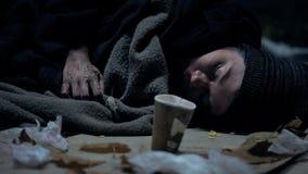 Άρρωστος βρώμικος ύπνος επαιτών στην οδό, το φλυτζάνι εγγράφου εδώ κοντά, τη φιλανθρωπία και τη δωρεά στοκ εικόνα με δικαίωμα ελεύθερης χρήσης