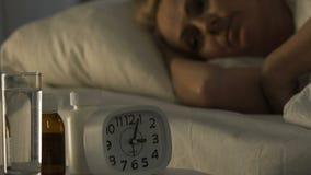 Άρρωστος θηλυκός συνταξιούχος που βρίσκεται στο κρεβάτι και που πάσχει από την αϋπνία, προβλήματα υγείας απόθεμα βίντεο