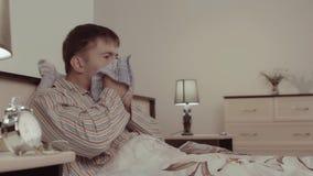 Άρρωστος νεαρός άνδρας που βρίσκεται στο κρεβάτι και το φτέρνισμα απόθεμα βίντεο