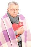 Άρρωστος πρεσβύτερος με το θερμόμετρο στο στόμα του, που καλύπτεται με το κάλυμμα Στοκ Φωτογραφία