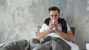 Άρρωστος χιλιετής τύπος που εξετάζει τη κάμερα πίνοντας το τσάι απόθεμα βίντεο