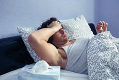 Άρρωστο άτομο που φαίνεται θερμοκρασία στο θερμόμετρο στο κρεβάτι Στοκ Φωτογραφίες