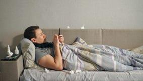 Άρρωστο άτομο που χρησιμοποιεί το smartphone στον καναπέ στοκ εικόνα