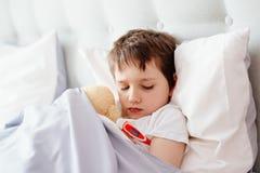 Άρρωστο αγοράκι στο κρεβάτι με ένα θερμόμετρο Στοκ εικόνες με δικαίωμα ελεύθερης χρήσης