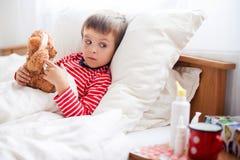 Άρρωστο αγόρι παιδιών που βρίσκεται στο κρεβάτι με έναν πυρετό, στήριξη Στοκ Εικόνα